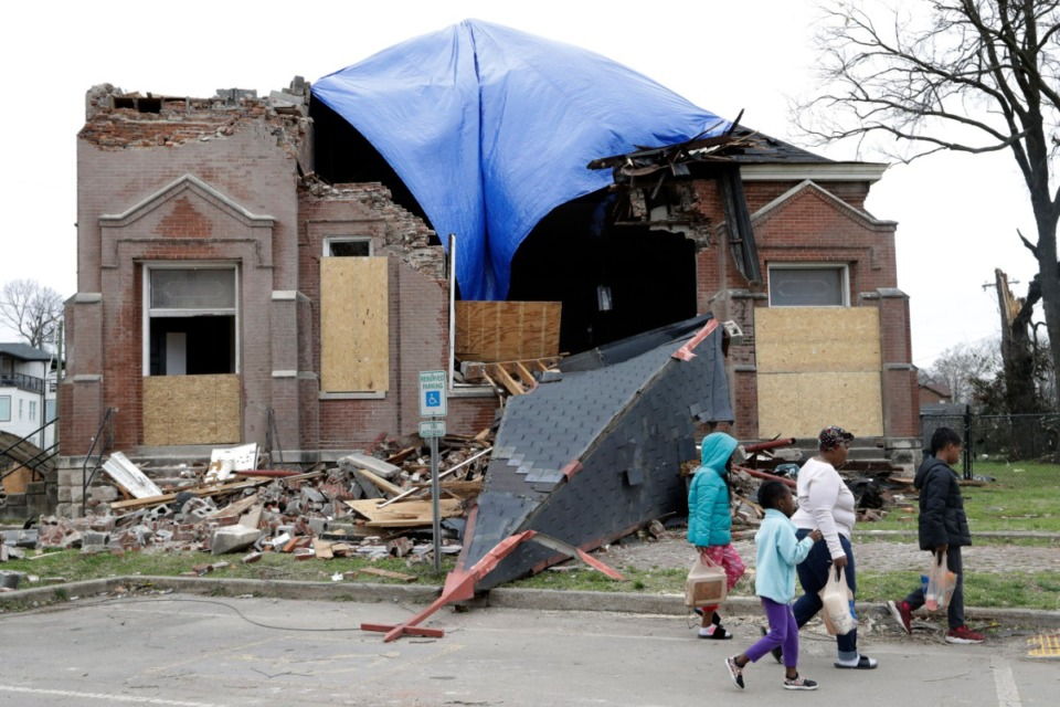<strong>People pass by damaged Hopewell Missionary Baptist Church on March 4, 2020, in Nashville. Tornadoes hit the state the day before and a grim search continues for survivors of the deadly storms that killed at least 24 people and left many others missing.</strong> (AP Photo/Mark Humphrey)