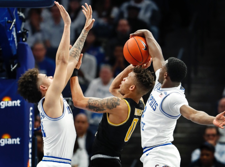 <strong>Alex Lomax (right) blocks Wichita State guard Dexter Dennis (middle) as teammate Lester Quinones (left) helps March 5, 2020, at FedExForum.</strong> (Mark Weber/Daily Memphian)