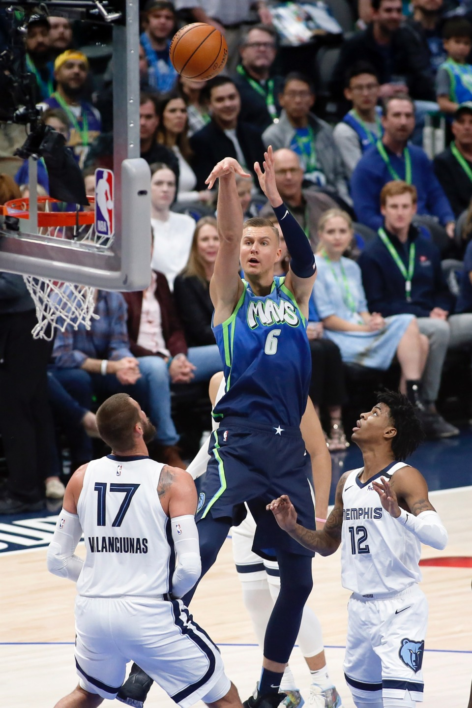<strong>Dallas Mavericks forward Kristaps Porzingis (6) shoots the three-point basket over Memphis Grizzlies center Jonas Valanciunas (17) and guard Ja Morant (12) during the first half of an NBA basketball game in Dallas, Friday, March 6, 2020.</strong> (AP Photo/Ray Carlin)