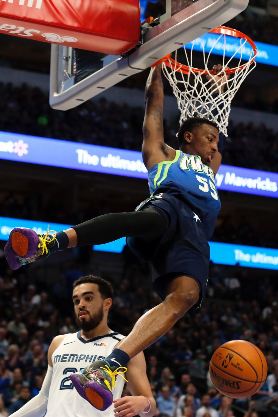 <strong>Dallas Mavericks guard Delon Wright, top, follows through on a dunk over Memphis Grizzlies guard Tyus Jones, bottom, during the first half of an NBA basketball game in Dallas, Friday, March 6, 2020.</strong> (Ray Carlin/AP)