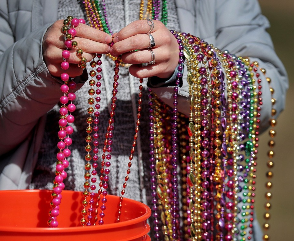 <strong>Lui Zeballos passes out Mardi Gras beads during a&nbsp;Mardi Growl dog party at Overton Park on March 7, 2020. The event included a costume contest and parade hosted by the Overton Park Conservancy and Hollywood Feed.</strong> (Jim Weber/Daily Memphian)