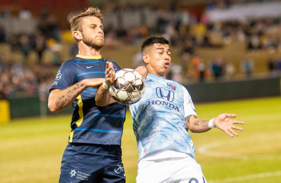 <strong>Memphis 901 FC defender Zach Carroll goes for the ball against Indy Eleven forward Yeferson Contreras during Saturday's season opener at AutoZone Park.</strong> (Greg Campbell/Special to The Daily Memphian)