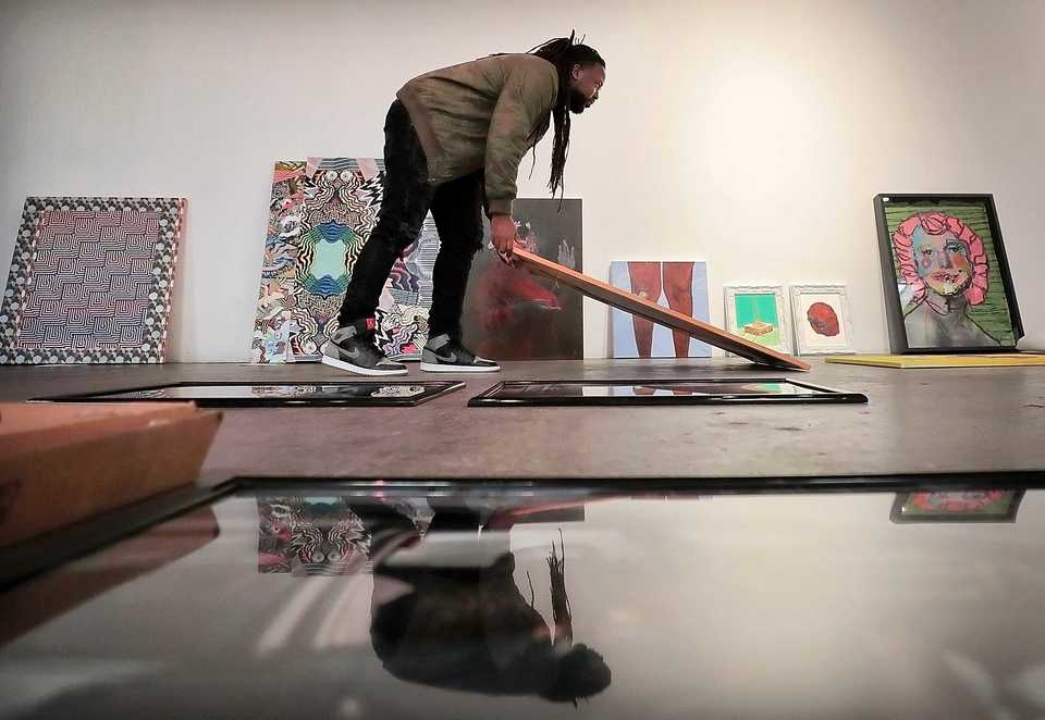 "<strong>Jamond Bullock rearranges pieces before installing the ""Young Gifted &amp; Dope, Episode 2"" art show at Marshall Arts on Nov. 16, 2018. The show features 19 artists from Memphis or with Memphis connections showing their respective art to a soundtrack curated by Lyfe is Dope.</strong> (Jim Weber/Daily Memphian)"