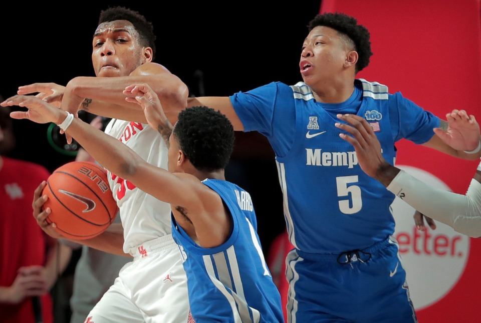 <strong>Houston Forward Fabian White (left) fends off University of Memphis guard Boogie Ellis (5) and Tyler Harris after a rebound during the Tigers' game against the Cougars at the Fertitta Center in Houston on March 8, 2020.</strong> (Jim Weber/Daily Memphian)