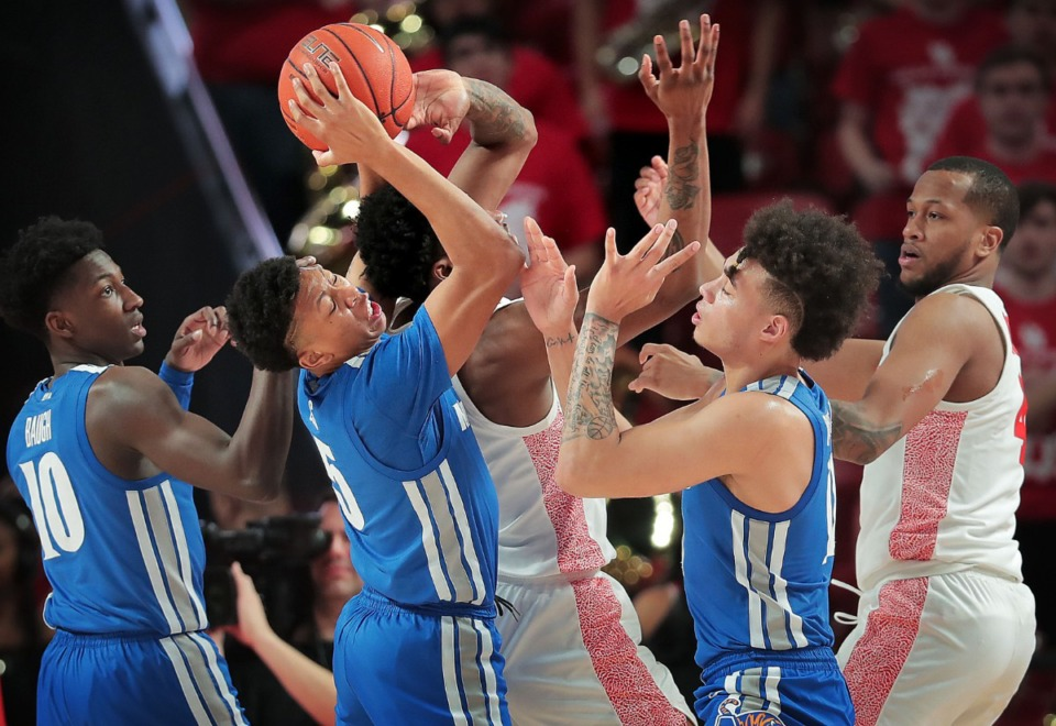 <strong>University of Memphis guards Damion Baugh (10) Boogie Ellis (5) and Lester Quinones battle for control of a rebound during the Tigers' game against the Cougars at the Fertitta Center in Houston on March 8, 2020.</strong> (Jim Weber/Daily Memphian)