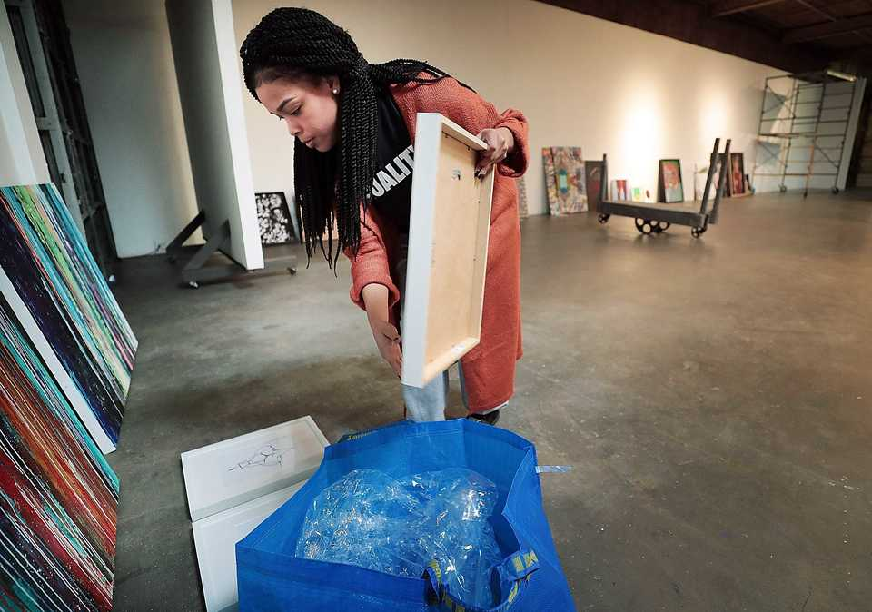 "<strong>Artist Alexis Miche delivers several pieces including a series called ""Sitting Plenty"" as Jamond Bullock gets ready to install the ""Young Gifted &amp; Dope, Episode 2"" art show at Marshall Arts on Nov. 16, 2018.&nbsp;</strong>(Jim Weber/Daily Memphian)"