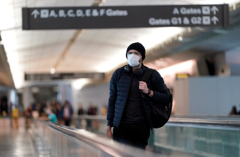 <strong>An airline passenger wearing a mask makes his way through the International Terminal at San Francisco International Airport Saturday, March 7, 2020, in San Francisco. As cases of the coronavirus surge in Italy, Iran, South Korea, the U.S. and elsewhere, many scientists say it's plain that the world is in the grips of a pandemic &mdash; a serious global outbreak.</strong> (David J. Phillip/AP)