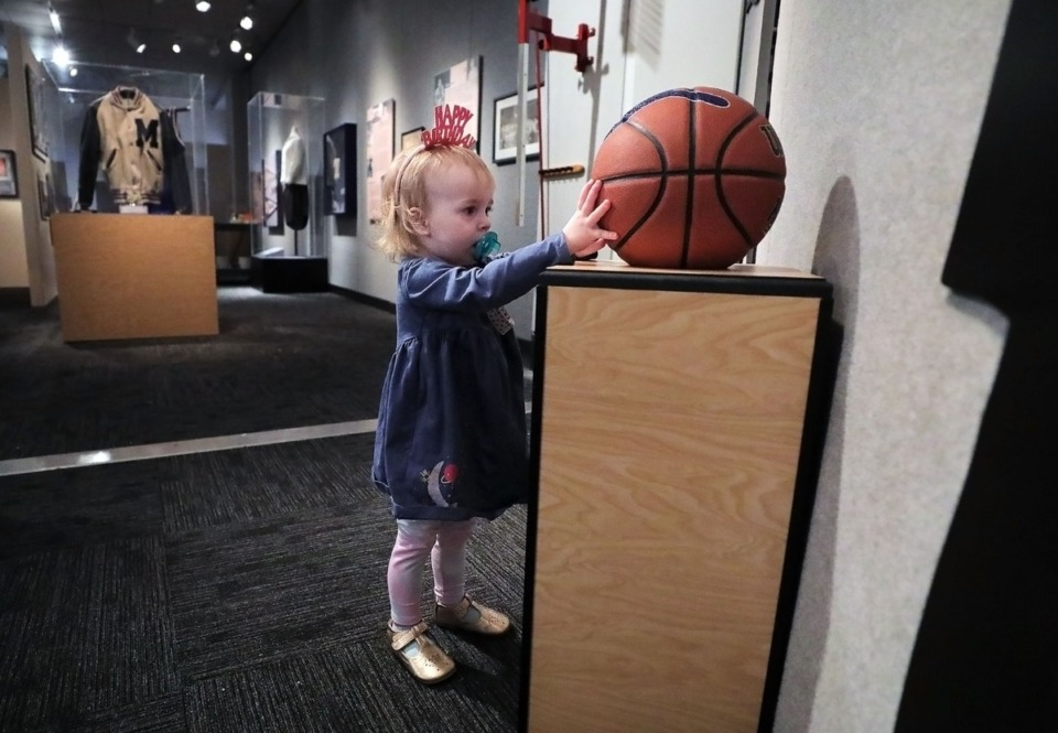 <strong>During a visit to the Pink Palace on Friday, March 6, Rosalie Gibson, whose mother works at the museum, compares her hand to that of a University of Memphis basketball player at a new exhibit on the history of the U of M men's and women's basketball programs.</strong> (Patrick Lantrip/Daily Memphian)