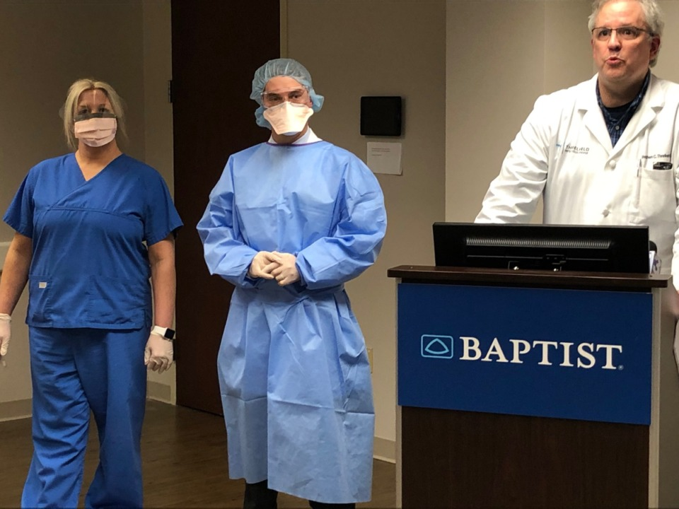 <strong>Dr. Stephen Threlkeld (at podium) shows the protective gear staff working with COVID-19 patients wear at the Baptist Memorial Hospital-Memphis press conference March 9, 2020.</strong> (Jane Roberts/Daily Memphian)