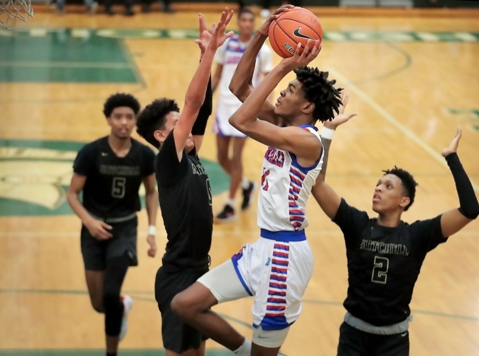 <strong>Wooddale's Johnathan Lawson (center) shoots under pressure on Feb. 15, 2020. Lawson joins his older brother Dedric as a winner of the Mr. Basketball award.</strong> (Jim Weber/Daily Memphian file)