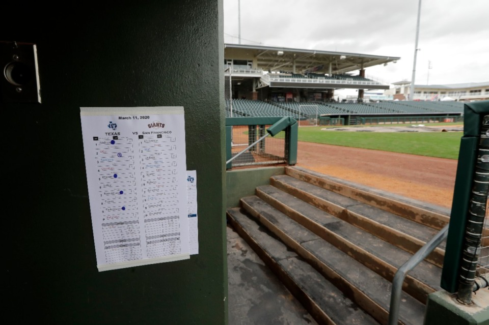 <strong>A line-up sheet from the previous day's baseball game is posted on the wall of an otherwise empty dugout and ballpark after the cancellation of the spring training baseball game between the Kansas City Royals and the Seattle Mariners in Surprise, Ariz., on Thursday, March 12. Major League Baseball is delaying the start of its season by at least two weeks because of the coronavirus outbreak and has suspended the rest of its spring training game schedule.</strong> (Elaine Thompson/Associated Press)