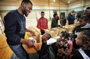 <strong>Zamarion Boyd, 5, argues with former Memphis Grizzlies player Tony Allen (left) that he is big enough to carry the turkey as the Grindfather greets families in person while passing out Thanksgiving meals at Streets Ministries on Nov. 17, 2018.</strong> (Jim Weber/Daily Memphian)