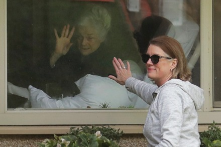 <strong>Judie Shape (left), who has tested positive for the COVID-19 coronavirus, waves as her daughter, Lori Spencer, puts her hand on the window at the end of their visit over the phone Wednesday, March 11, at the Life Care Center in Kirkland, Wash., near Seattle. In-person visits are not allowed at the nursing home, which is at the center of the outbreak of the COVID-19 coronavirus in Washington state.</strong> (Ted S. Warren/Associated Press)