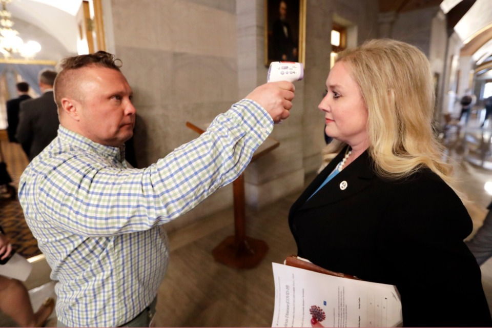 <strong>Tennessee Health Commissioner Lisa Piercey has her temperature taken by Scott Wyatt, left, of the Tennessee Department of Health as Piercey arrives for a news conference concerning the state's response to the coronavirus Monday, March 16, 2020, in Nashville.</strong> (Mark Humphrey/AP