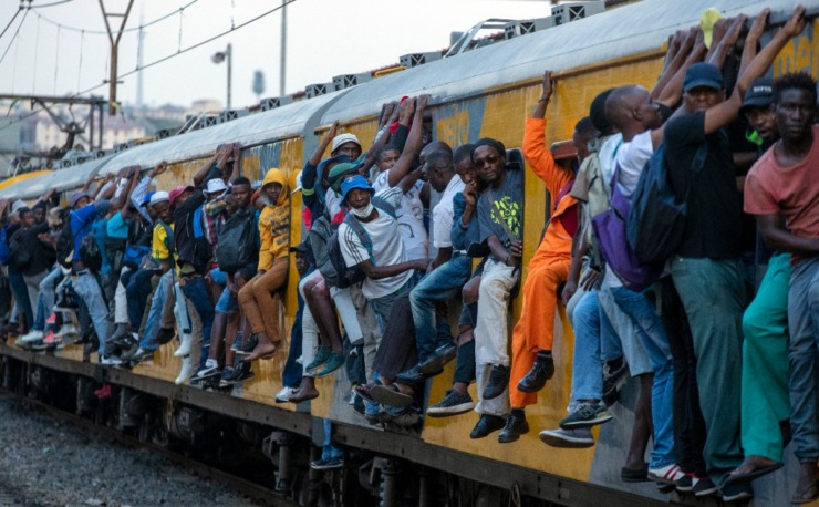 <strong>Train commuters hold on to the side of an overcrowded passenger train in Soweto, South Africa, Monday, March 16, 2020. South Africa will revoke nearly 10,000 visas issued this year to people from China and Iran, and visas will now be required for other high-risk countries that had been visa-free, including Italy and the United States. </strong>(Themba Hadebe/AP)