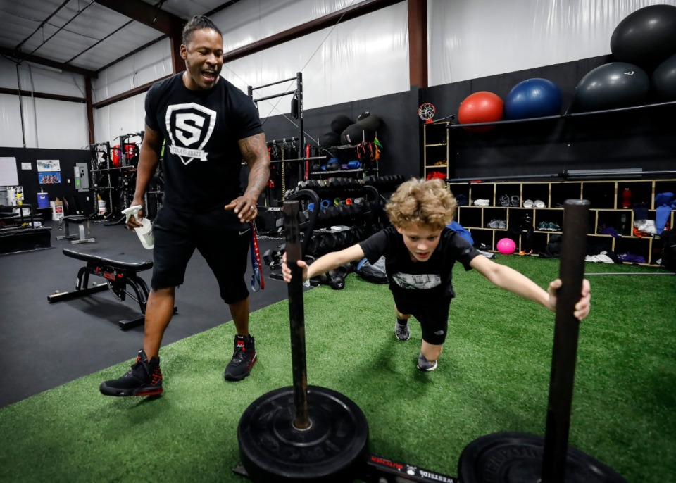 <strong>Local trainer Raheem Shabazz motivates Joe Micheal, 10, who is working on his leg strength at Shabazz's training facility in Cordova on Friday, March 13.</strong> (Mark Weber/Daily Memphian)