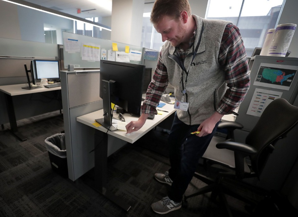 <strong>ServiceMaster employee Nick Eddy disinfects his cubicle with bleach wipes at the ServiceMaster headquarters in Downtown Memphis on Tuesday, March 17. Many corporations are shifting to working remotely and others are ramping up their cleaning regimen due to COVID-19.</strong> (Jim Weber/Daily Memphian)