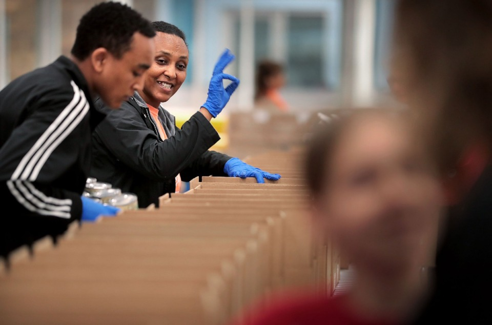 <strong>Alem Worku signals down the line as volunteers gather in groups of 10 to work an assembly line on March 17, 2020, at the Midsouth Food Bank warehouse, where they were putting together 14-day food kits for needy families in Memphis. The Food Bank is trying to assemble 50,000 kits consisting of 25 pounds of canned vegetables, canned fruit, peanut butter, oatmeal and rice to feed families that may be forced into isolation by COVID-19.</strong> (Jim Weber/Daily Memphian)