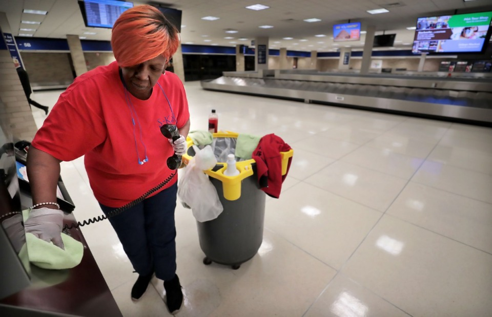 <strong>Janitorial contractor Angela Jones wipes down phones and handrails in the deserted baggage claim area at Memphis International Airport on March 13, 2020. In addition to adding more cleaning staff to clean and disinfect, the airport has temporarily closed the C terminal checkpoint as well as Maggie O'Shea's and Moe's Southwestern Grill restaurants because passenger numbers have fallen significantly below projections during an expected spring break peak time due to COVID-19</strong>. (Jim Weber/Daily Memphian)