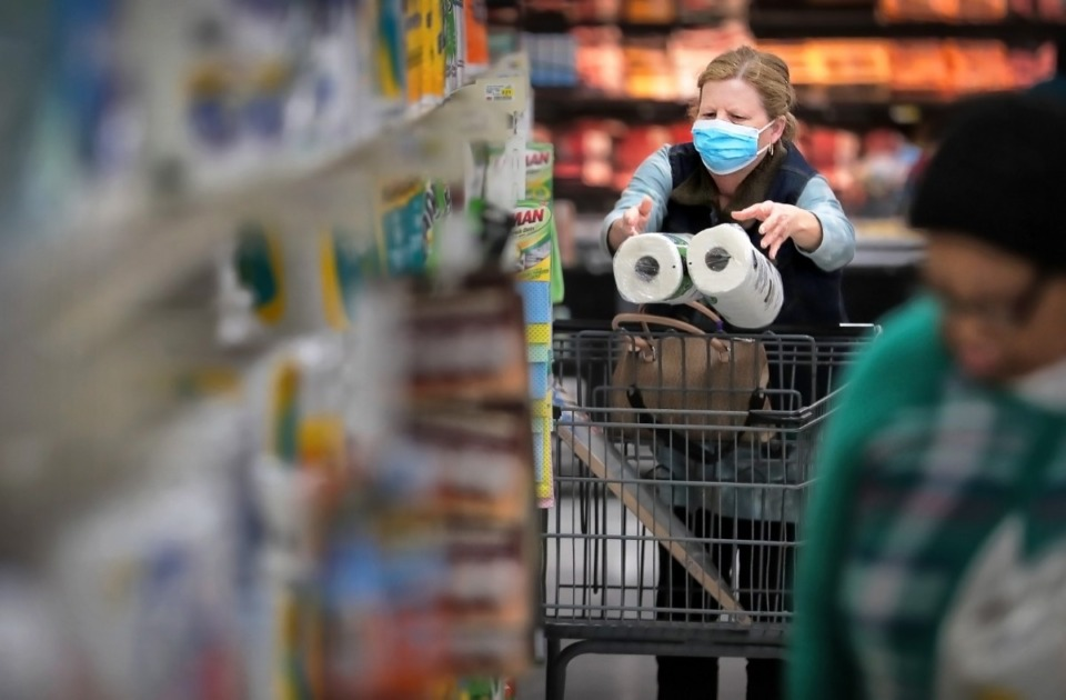 <strong>Deeanna Beene shops for paper goods during a busy day at the CashSaver in Midtown Memphis on March, 12, 2020, where there were some shortages on cleaning wipes and disinfectant as customers fearful of COVID-19 try to stock up. Beene says her doctor suggested she wear a mask because she might be at an elevated risk due to her age and diabetes.</strong> (Jim Weber/Daily Memphian)