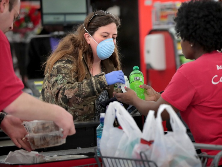 <strong>Crystal Dannell picks up a few snacks during a busy day at the CashSaver in Midtown Memphis on March, 12, 2020, where there were some shortages on cleaning wipes and disinfectant as customers fearful of COVID-19 try to stock up. Dannell has been visiting her brother, who suffers from leukemia, at the hospital and was asked to take extra precautions while out.</strong> (Jim Weber/Daily Memphian)