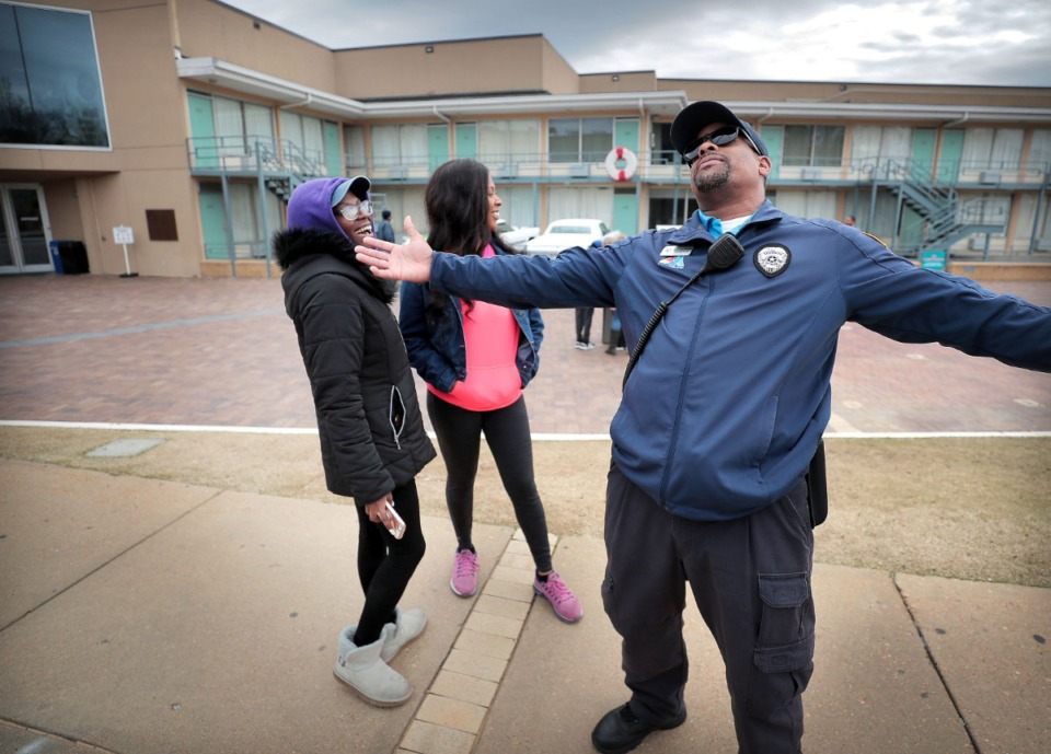 <strong>Terrance Miller, a member of the Blue Suede Brigade, jokes with spring breakers Devina Lias (left) and Cherish Bridges in front of the National Civil Rights Museum on March 13, 2020. Miller is looking at a serious loss of income from his side gig with FedExForum security as sporting events and concerts get cancelled due to COVID-19.</strong> (Jim Weber/Daily Memphian)
