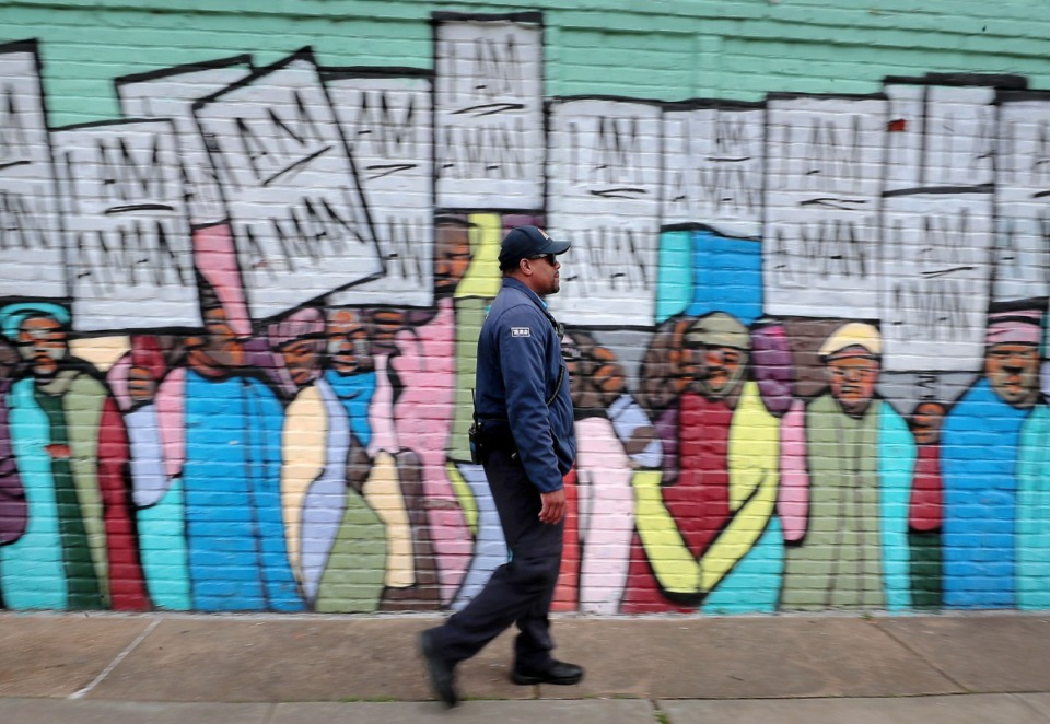 "<strong>Terrance Miller, a member of the Blue Suede Brigade, passes by the ""I am a man"" mural on South Main while walking his route near the National Civil Rights Museum on March 13, 2020. Miller is looking at a serious loss of income from his side gig with FedExForum security as sporting events and concerts get cancelled due to COVID-19.</strong> (Jim Weber/Daily Memphian)"