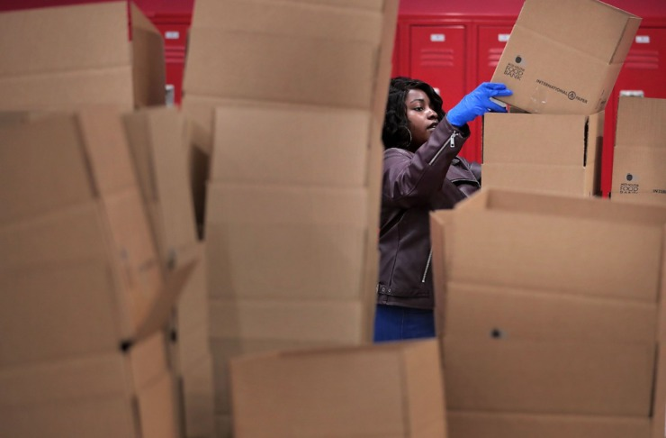 <strong>Ariel Wade assembles boxes as volunteers gather in groups of 10 to work an assembly line on March 17, 2020, at the Midsouth Food Bank warehouse putting together 14-day food kids for needy families in Memphis.</strong>&nbsp;<strong>The Food Bank is trying to assemble 50,000 kits consisting of 25 pounds of canned, vegetables, canned fruit, peanut butter, oatmeal and rice to feed families that may be forced into isolation by COVID-19.&nbsp;</strong>(Jim Weber/Daily Memphian)
