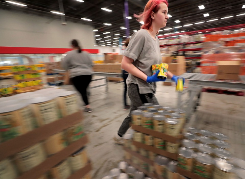 <strong>Ellen Barnes boxes up cans of fruit as volunteers gather in groups of 10 to work an assembly line on March 17, 2020, at the Midsouth Food Bank warehouse putting together 14-day food kids for needy families in Memphis. The Food Bank is trying to assemble 50,000 kits consisting of 25 pounds of canned, vegetables, canned fruit, peanut butter, oatmeal and rice to feed families that may be forced into isolation by COVID-19.&nbsp;</strong>(Jim Weber/Daily Memphian)