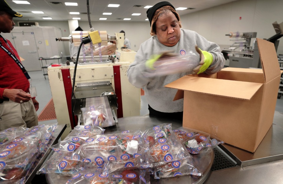 <strong>Deltha Earnest boxes up shrink-wrapped packages as food prep workers at the SCS Nutrition Services center sort meals slated for delivery to a local community center on March 18, 2020. The SCS Nutrition Services Center will be ramping up production next week as the school district makes plans to distribute meals from some 60 sites that students on the school lunch program will be able to take home.</strong> (Jim Weber/Daily Memphian)
