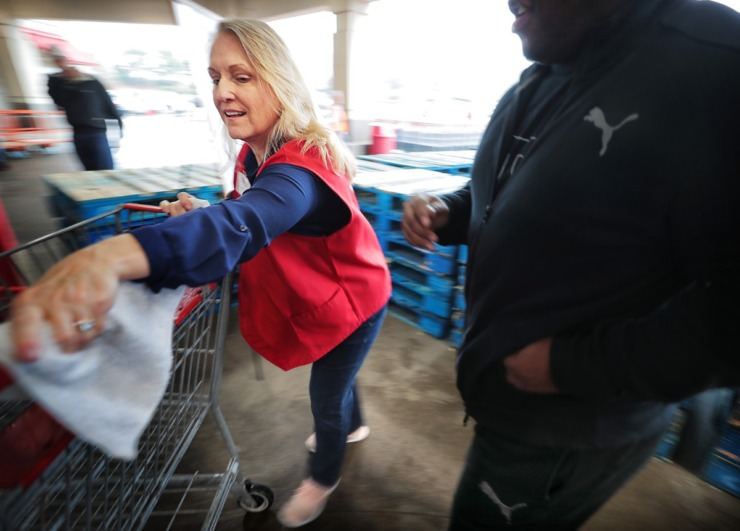 <strong>Costco employee Jodie Bowden disinfects grocery cart handles for customers as the enter the busy Costco on Germantown Parkway where management attempts to comply with federal social distancing guidelines by allowing 10-20 customers into the store periodically, a policy designed to control checkout lines and crowding.</strong> (Jim Weber/Daily Memphian)