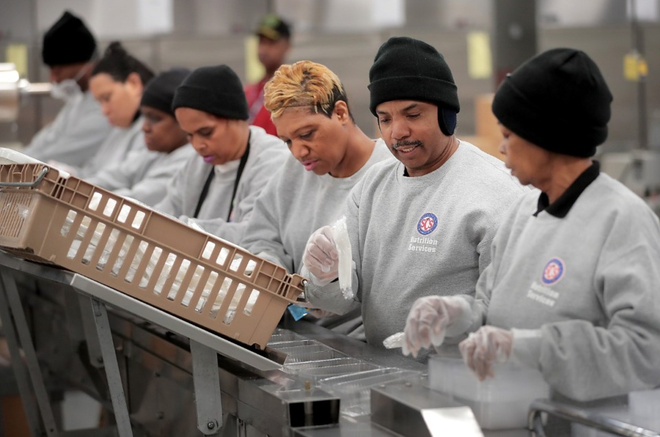 <strong>Claudia Diggs (right), Stanley Cooke and Jennifer Dennis join a line of food prep workers at the SCS Nutrition Services center to sort meals slated for delivery to a local community center on March 18, 2020. The SCS Nutrition Services Center will be ramping up production next week as the school district makes plans to distribute meals from some 60 sites that students on the school lunch program will be able to take home.&nbsp;</strong>(Jim Weber/Daily Memphian)