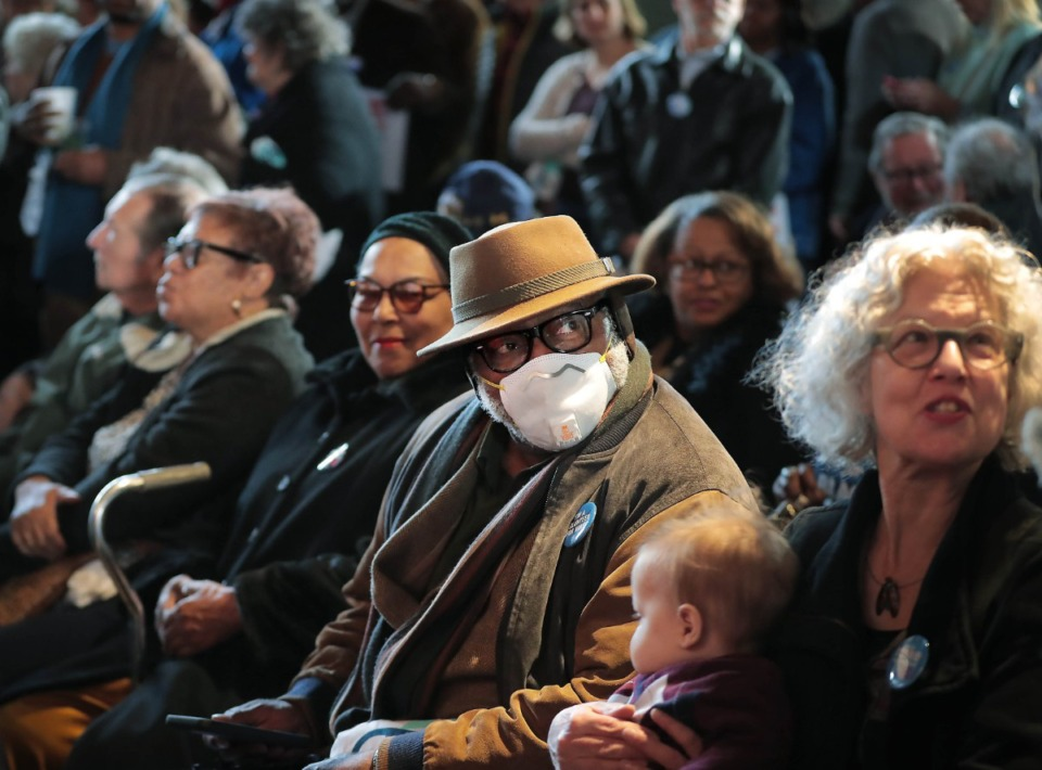 "<strong>Concerned about catching ""A cold or coronavirus, or just getting sick,"" Ernest Trice dons a mask in a crowd of Bloomberg supporters at Minglewood Hall as Democratic presidential contender Michael Bloomberg delivers his stump speech during a campaign stop in Memphis on Feb. 28, 2020.</strong> (Jim Weber/Daily Memphian)"