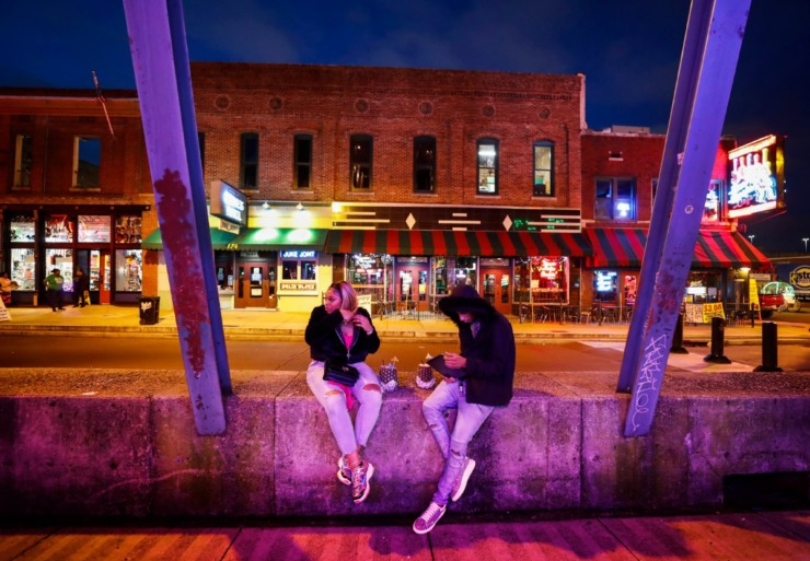 <strong>Kendrica Wright and Lee Williams sit on an empty Beale Street on St. Patrick's</strong><strong> Day on Tuesday, March 17, 2020. Area restaurants and bars are experiencing a smaller number of customers due to the outbreak of coronavirus.</strong> (Mark Weber/Daily Memphian)