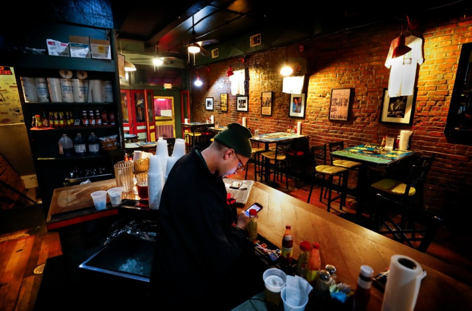 <strong>Miss Polly's waiter Eli Wheeler scans his cell phone during an unusually slow&nbsp;St. Patrick's Day on Tuesday, March 17, 2020. Area restaurants and bars are experiencing a smaller number of customers due to the outbreak of coronavirus.</strong> (Mark Weber/Daily Memphian)&nbsp;