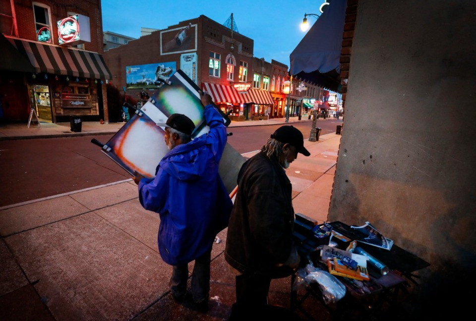 <strong>Artists Carl Brown (left) and Ernest Lawson (right) pack up their supplies around 7:30 p.m.&nbsp;on St. Patrick's Day on Tuesday, March 17, 2020. Area restaurants and bars are experiencing a smaller number of customers due to the outbreak of coronavirus. </strong>(Mark Weber/Daily Memphian)