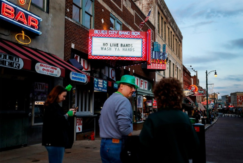 <strong>Tourists celebrating St. Patrick's Day on Beale Street on Tuesday, March 17, 2020, walk by the Blues City Cafe &amp; Band Box billboard stating they temporarily will not have live music.</strong> (Mark Weber/Daily Memphian)