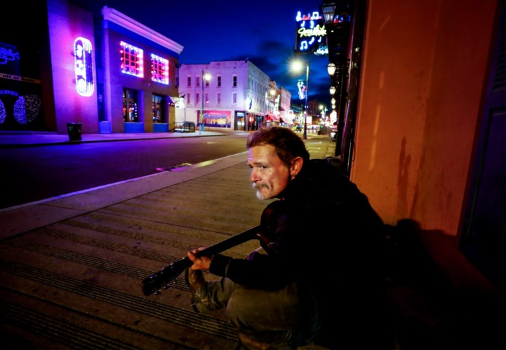 <strong>Musician Jamie Kenton strums his guitar on a vacant Beale Street on St. Patrick's Day Tuesday, March 17, 2020.&nbsp;</strong> (Mark Weber/Daily Memphian)