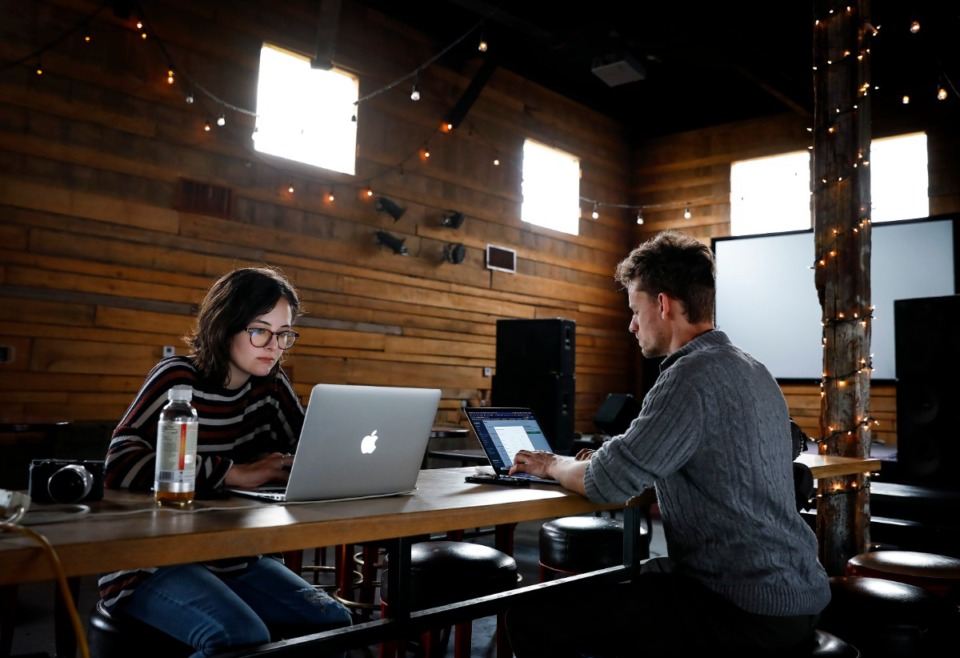<strong>ITS Fine Restaurant Group social media team members Bella Golightly (left) and Miles Kovarik (right) strategize ideas to help displaced servers on Wednesday, March 18, 2020, at Loflin Yard. Earlier that day, the local restaurant group announced the closure of several properties and employee layoffs due to the outbreak of the coronavirus. Golightly, Kovarik and others in the group are looking for creative ways to help laid-off employees earn income during these trying times.</strong> (Mark Weber/Daily Memphian)