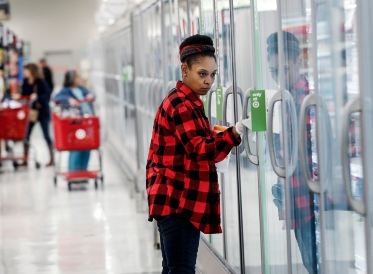 <strong>Shanetha Russell wipes down refrigerator doors with cleaning wipes at the Target Memphis Central Store on Wednesday, March 18, 2020.</strong> (Mark Weber/Daily Memphian)
