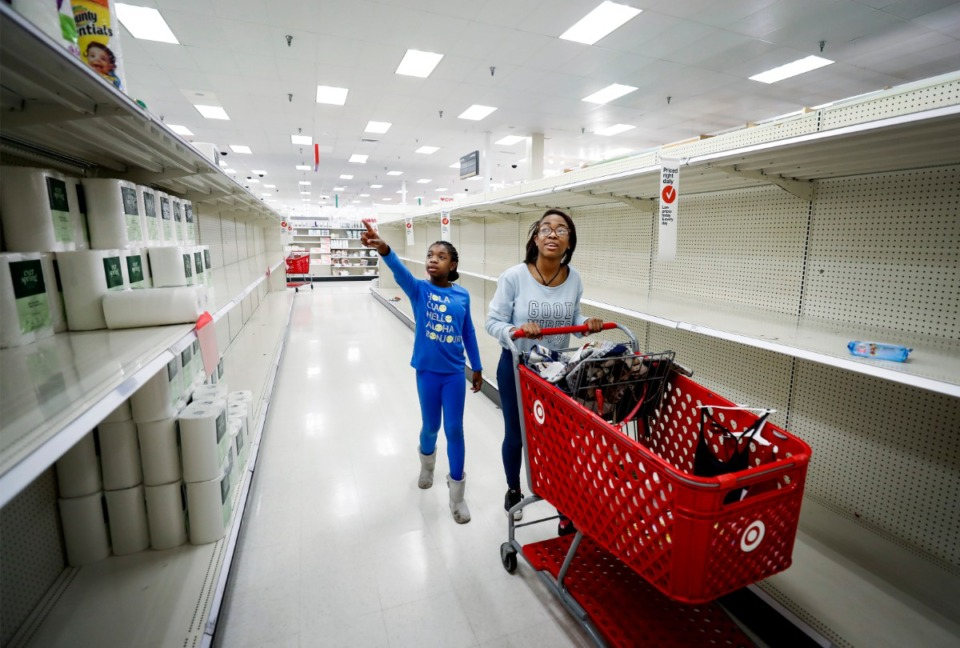 <strong>Es'ynce Woodruff, 9, (left) points to rolls of paper towels while shopping with Paris Hall (right) at the Target Memphis Central Store on Wednesday, March 18, 2020. Since the outbreak of the coronavirus, the store replaces their paper good supplies daily and by the afternoon they are gone.</strong> (Mark Weber/Daily Memphian)