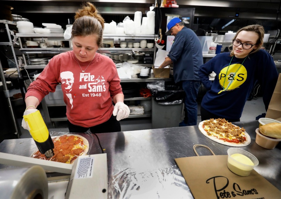 <strong>Pete &amp; Sam&rsquo;s Italian Restaurant&rsquo;s Jennifer Sing (left) and Mia Bomerito (right) shrink-wrap pizzas that will be frozen and used for delivery or pickup orders. On March 17, 2020, the restaurant began shifting to producing more pre-made items that will be used for delivery and pickup orders&nbsp; in the wake off social distancing due to the coronavirus pandemic.</strong> (Mark Weber/Daily Memphian)