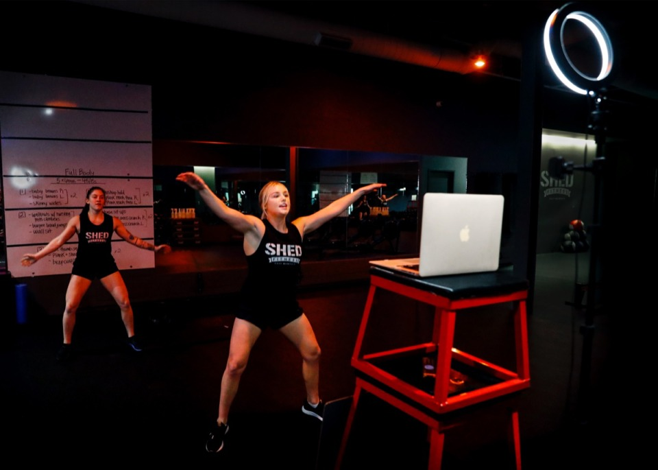 <strong>Instructors Jenny Gee (front) and Olivia Ross (back) perform exercises while doing a livestream workout broadcast with clients at SHED Fitness on Thursday, March 19, 2020.</strong> (Mark Weber/Daily Memphian)