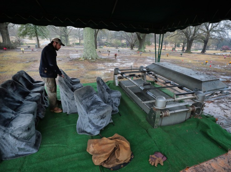 <strong>Juaquin Maya with Southern Vault Co. prepares a burial site in Memorial Park Cemetery for a funeral later in the day on March 18, 2020, keeping in mind new government guidelines for social distancing as he set out chairs despite the limitations created by the dimensions of the tent.</strong> (Jim Weber/Daily Memphian)