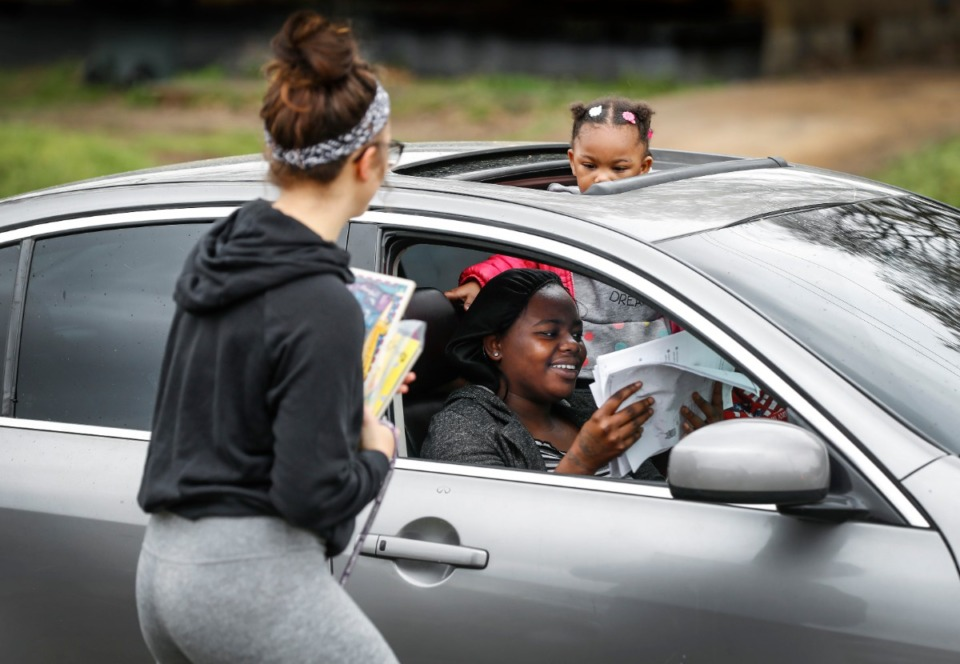 <strong>Autumn Robison, 2, peers out from a sunroof as her aunt Carlesha Chearie gets classwork from first-grade teacher Tylor Beardall (left) at KIPP Memphis Preparatory Elementary school on Friday, March 20.</strong> (Mark Weber/Daily Memphian)