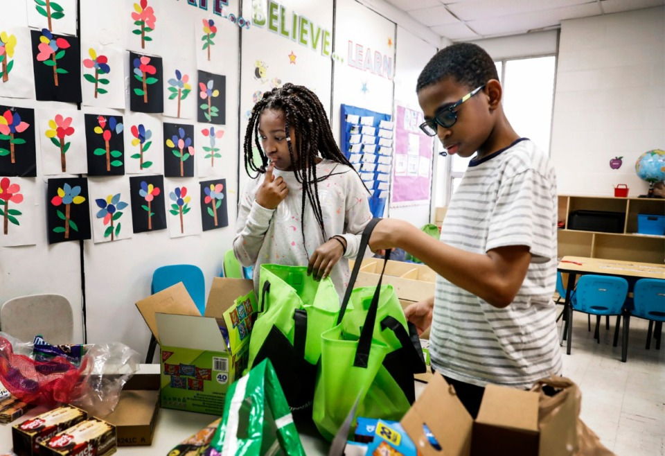 <strong>Kalynn Allen, 10, (left) ponders which donated supplies to grab while filling bags on Friday, March 20, with Vincent Martin, 12, that will be given to parents at KIPP Memphis Preparatory Elementary school.</strong> (Mark Weber/Daily Memphian)