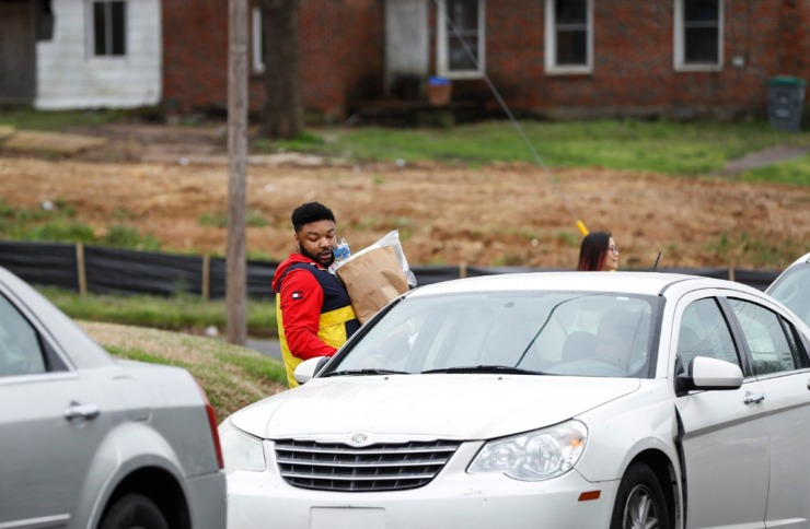 <strong>Third grade teacher Franklin LeSueur hands out donated supplies and classwork to parents at KIPP Memphis Preparatory Elementary school on Friday, March 20, 2020.</strong> (Mark Weber/Daily Memphian)