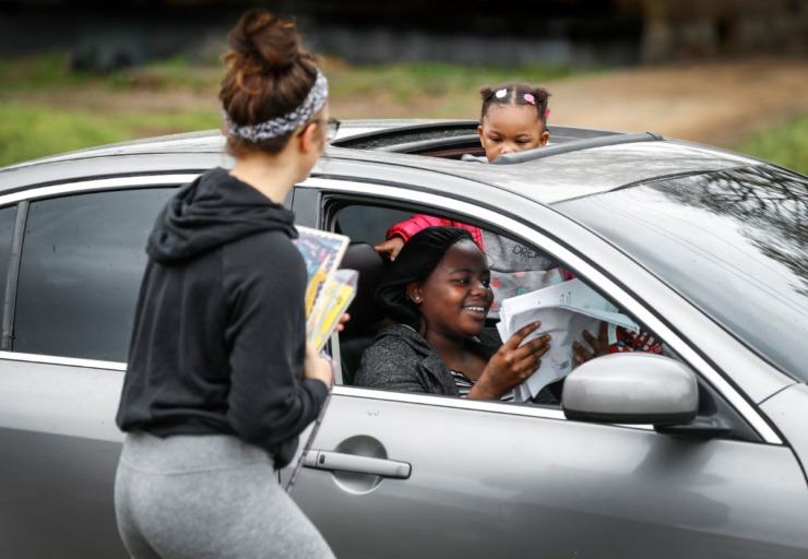 <strong>Autumn Robison, 2, pears out from a sunroof as her aunt Carlesha Chearie (bottom) grabs classwork from 1st grade teacher Tylor Beardall (left) at KIPP Memphis Preparatory Elementary school on Friday, March 20, 2020.</strong> (Mark Weber/Daily Memphian)