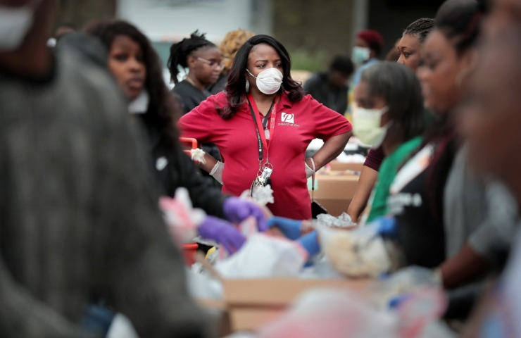 <strong>Pastor Sheila Floyd keeps an eye on things as members of the Pursuit of God Church in partnership with Life Church, Bellevue Baptist and Mid-South Food Bank assemble some 250 food baskets to give away to those in need on March 20, 2020 at Pursuit of God Church in Frayser.</strong> (Jim Weber/Daily Memphian)
