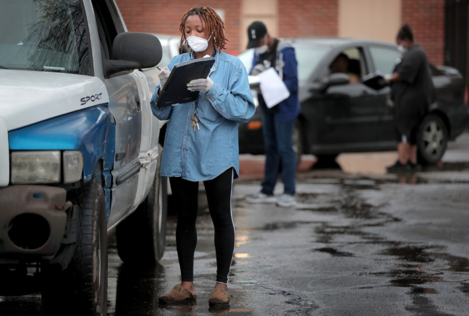 <strong>Christina Floyd gathers information during a drive-through food drive as members of the Pursuit of God Church in partnership with Life Church, Bellevue Baptist and Mid-South Food Bank assemble some 250 food baskets to give away to those in need on March 20, 2020 at Pursuit of God Church in Frayser.</strong> (Jim Weber/Daily Memphian)